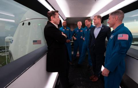 SpaceX founder Elon Musk (left), NASA astronauts Victor Glover, Doug Hurley, Bob Behnken, NASA Administrator Jim Bridenstine, and NASA astronaut Mike Hopkins are seen inside the crew access arm with the SpaceX Crew Dragon spacecraft visible behind them