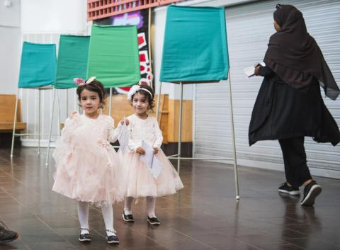 Dos niñas posan ante la cámara mientras sus padres votan en unas elecciones celebradas en Suecia.
