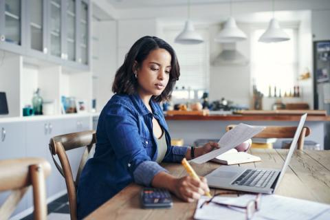 Una mujer revisa documentos mientras teletrabaja