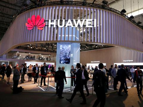 Visitors walk next to Huawei's booth at the Mobile World Congress 2019 in Barcelona.