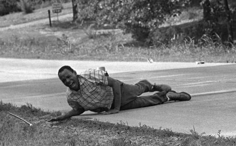 """James Meredith hace una mueca de dolor al cruzar la autopista 51 después de recibir un disparo en Hernando, Mississippi, durante la """"Marcha contra el miedo""""."""