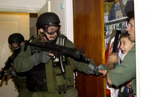 Elian Gonzalez se refugia en un armario protegido por Donato Dalrymple, uno de los hombres que rescataron al niño del mar.