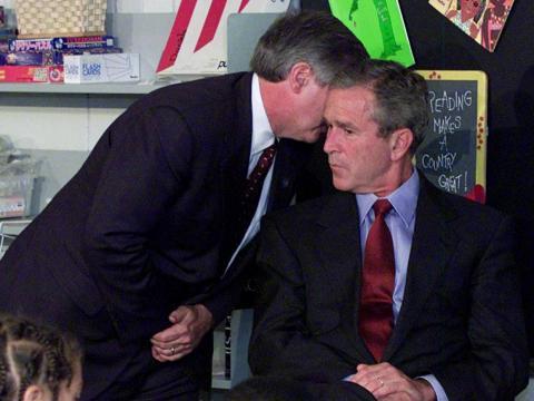 El jefe de personal del presidente Bush, Andy Card, susurra al oído del presidente durante una visita a la Escuela Primaria Emma E. Booker en Sarasota, Florida, el 11 de septiembre de 2001