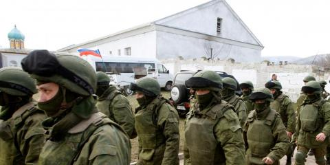 Armed men, believed to be Russian servicemen, walk outside a Ukrainian military base in Perevalnoye, near the Crimean city of Simferopol, March 14, 2014.