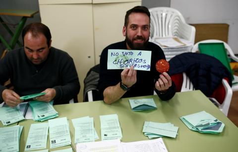Un miembro de una mesa electoral enseña el contenido de un sobre en Ronda, Málaga.