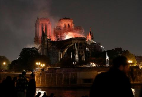 Firefighters doused flames from the burning Notre-Dame Cathedral as people looked on in Paris on Monday evening.