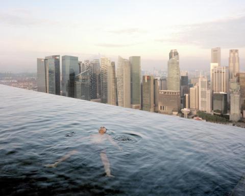 """""""Quería hacer un espectáculo que estuviera hecho de objetos preciosos y hermosos"""", dijo Little. En esta imagen, un hombre flota en la piscina del piso 57 del hotel Marina Bay Sands, con el horizonte del distrito financiero de Singapur"""