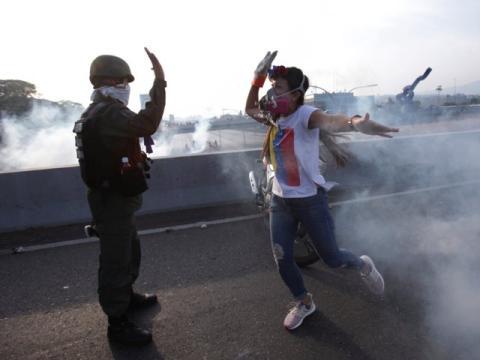 Una manifestante opositora saluda a un soldado fiel a Guaidó ante la base de La Carlota, Caracas
