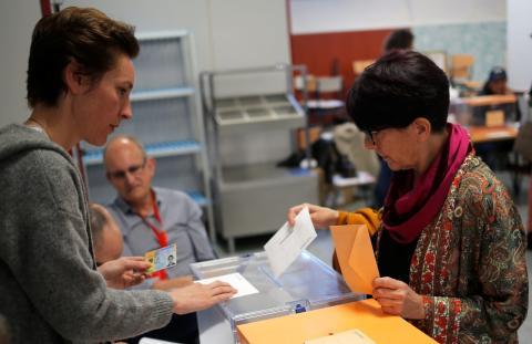 Una mujer deposita su voto en las urnas de las Elecciones Generales de 2019