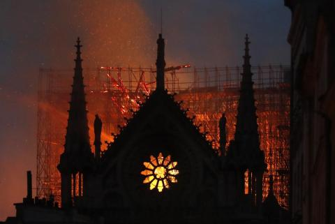 A silhouette of the Notre Dame Cathedral against the glow of the fire