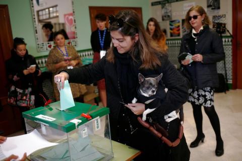 Una chica vota con su perro en las elecciones andaluzas de 2018, en Málaga.