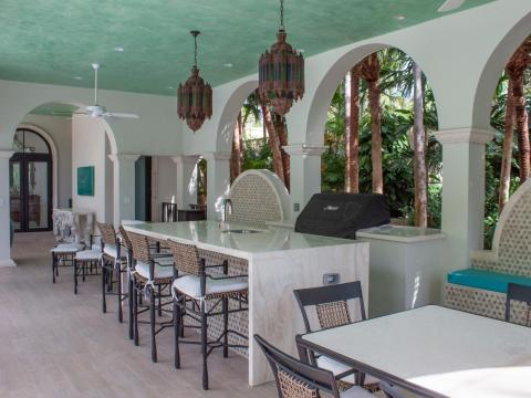 The cabana comes with a grill and kitchen area, and it's outfitted with a TV, lanterns, and ceiling fans.