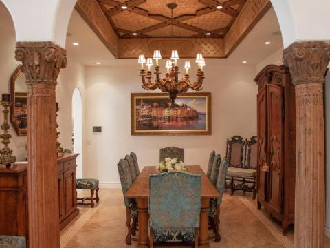 The formal dining room includes intricate wood detailing and a painting of Italy.