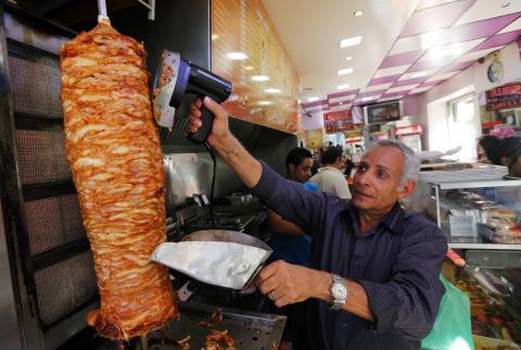 Un hombre corta un kebab.
