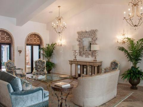 The home is opulently decorated, with high ceilings and chandeliers.