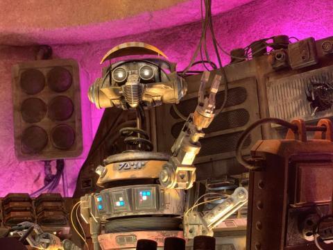 Dentro de uno de los restaurantes de la tierra, Oga's Cantina, DJ R-3X toca música para el público.