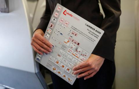 Una azafata sostiene una hoja con las instrucciones de seguridad en un avión de Laudamotion en Dusseldorf, Alemania.