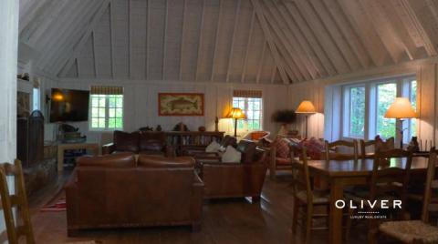 The main section of the house has a large living room with high ceilings and a wood-burning fireplace — a nice place to lounge after a long day at the lake or in the winter, after skiing on the nearby slopes.