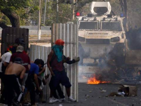 Manifestantes opositores se esconden de los tanques del Gobierno.