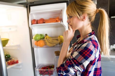 Mujer mirando el interior de un frigorífico