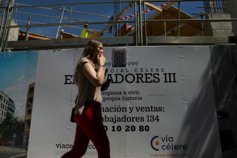 Una mujer pasa por delante de un cartel de una promoción de viviendas en venta en Madrid.