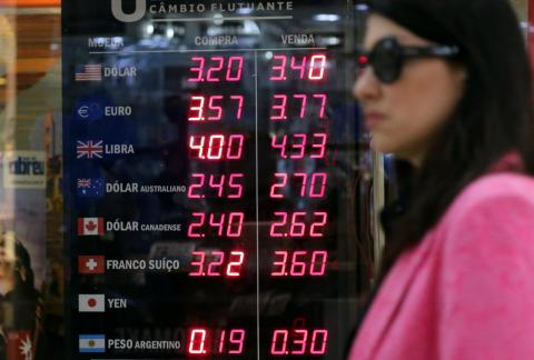 Una mujer pasea ante una oficina de cambio en Brasil