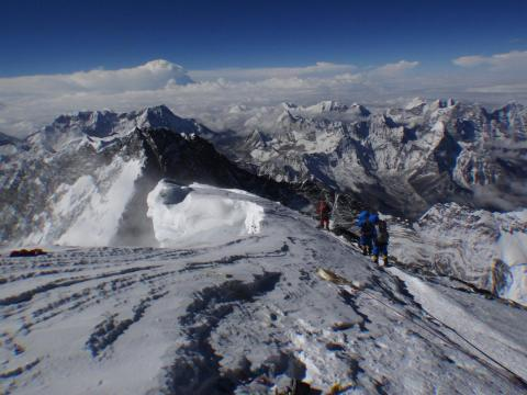 In this photograph taken on May 23, 2013 unidentified mountaineers look out from the summit of Mount Everest. Nepal marked 60 years since the first ascent of Everest May 29, celebrating the summiteers whose success has bred an