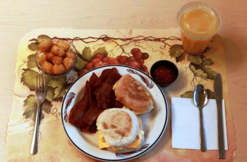 This processed breakfast includes egg mix, turkey bacon, and American cheese on an English muffin with a side of tater tots and ketchup. The orange juice was supplemented with extra fiber.