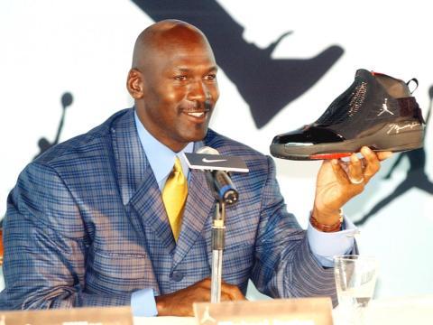La leyenda de la NBA Michael Jordan sostiene un zapato AJ19 autografiado, el último diseño de la línea de zapatos Air Jordan, en una conferencia de prensa en Hong Kong.
