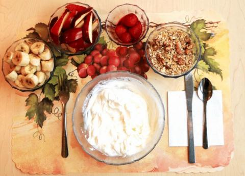 This unprocessed breakfast includes a Greek yogurt parfait with strawberries, bananas, walnuts, salt,olive oil, and apple slices with fresh squeezed lemon juice.
