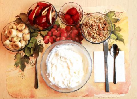Este desayuno sin procesar incluye yogurt griego con fresas, plátanos, nueces, sal, aceite de oliva y rodajas de manzana con zumo de limón recién exprimido.