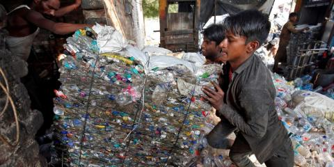 Workers pushing a bundle of crushed plastic bottles at a recycling factory in Ahmedabad, India, in November.