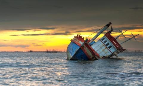 Un barco se hunde en el mar con el atardecer de fondo