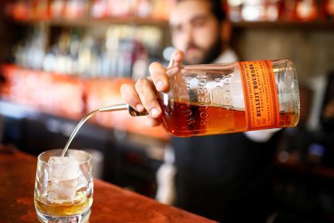 Un barista sirve una copa de whisky.