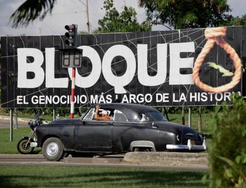 Un coche pasa ante un cartel cubano contra el embargo económico de EE.UU.