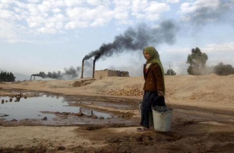 Aisha, de 11 años, transporta carbón para cocinar y calentar desde una fábrica de ladrillos en Jalalabad, el 17 de diciembre de 2013.