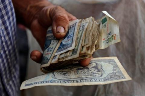 Un cubano con un fajo de billetes en la mano