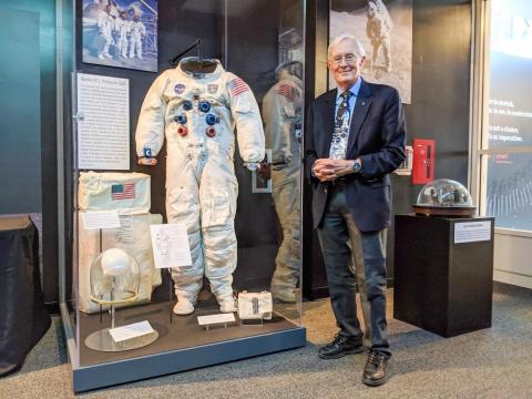 Duke, quien caminó por la luna en la misión del Apolo 16, posa junto al traje espacial en el Museo de los Orígenes de la Aviación de Nueva York.
