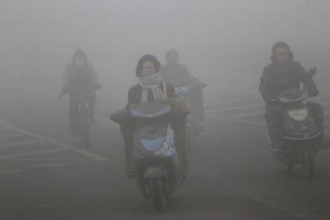 Ciclistas con máscaras viajan por una carretera con mucha niebla tóxica el 23 de diciembre de 2015 en Zhengzhou, China.