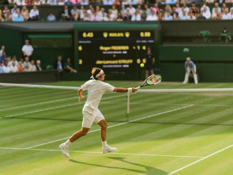 Federer hits a return at Wimbledon 2018.