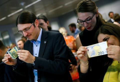 Gente tocando los nuevos billetes de 100 y 200 euros.