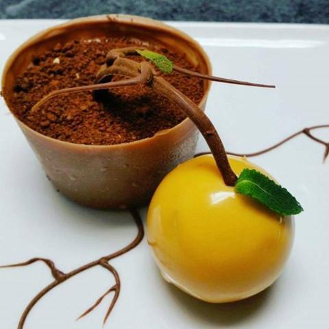 Una maceta de chocolate rellena de mousse de chocolate con ramas de árboles de chocolate y una naranja rellena con zumo de naranja recién exprimido.