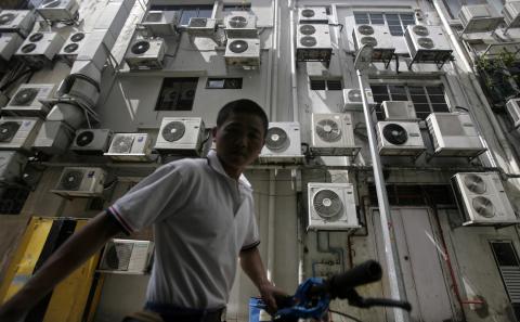 Hombre frente a un edificio repleto de aire acondicionado en Singapore.