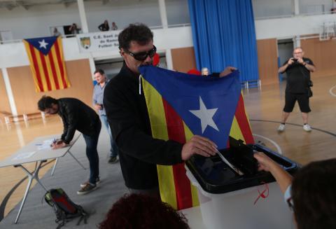 Un hombre vota con una estelada en un acto por el aniversario del 1-O