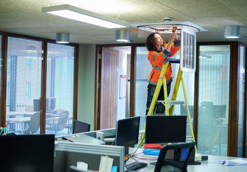 Una instaladora de aire acondicionado repara un equipo en una oficina