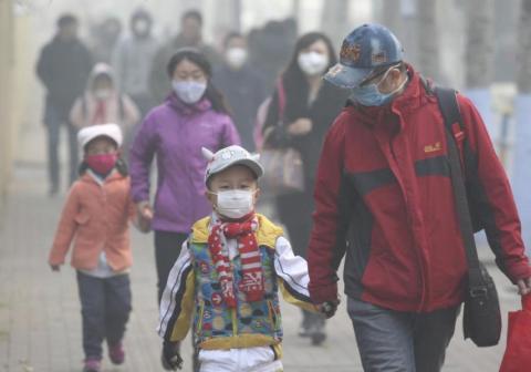 Jóvenes estudiantes y sus padres con máscaras caminan por una calle en un día nebuloso en Harbin, China, el 3 de noviembre de 2015.