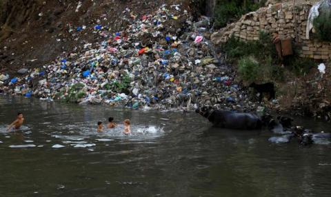 Unos niños nadan en un río contaminado cerca de un vertedero de basura en Rawalpindi, Pakistán.