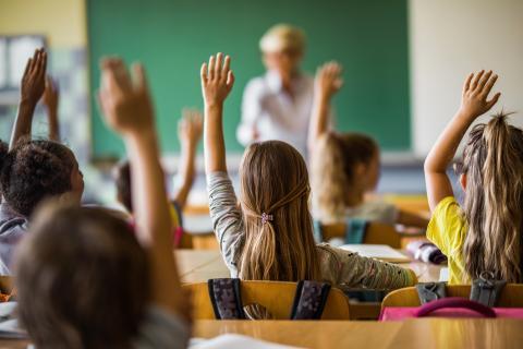 Niños en clase levantan la mano.