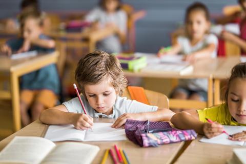 Niños escribiendo en clase.