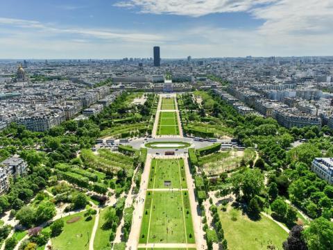 La Torre Eiffel de París se asoma al Champs de Mars, un gran parque público que atrae tanto a la población local como a los turistas.